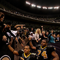 2009 November 30: New Orleans Saints running back Pierre Thomas (23) and offensive tackle Jermon Bushrod (74) celebrate with fans following a 38-17 win by the New Orleans Saints over the New England Patriots at the Louisiana Superdome in New Orleans, Louisiana.