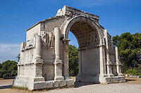 Glanum Arch - Glanum is an ancient city outside Saint-Rémy-de-Provence. Archaeological excavation on the site at Glanum has revealed an outstanding collection of architectural relics.  Set in the heart of the Alpilles mountains, the ancient city is steeped in Greek and Roman influence.<br /> The Triumphal Arch was built during the early Roman empire, indicating the entry road to Glanum along the great way of the Alps. The Mausoleum is the best-preserved mausoleum of the Roman world. Building during this first period had a Helenistic influence, using the technique of bonding using large carved stone blocks set together perfectly without mortar.  Early in the 1st century AD Glanum was forced to accept the status of a Roman colony. Following Ceasar's conquest of Marseille in 49 BC. Augustus rebuilt Glanum with Roman public buildings: forum, basilica, temples and baths.  From the early part of the first millineum until the 20th century the site was forgotten. The Triumphal Arch and Mausoleum, were noticeable beside the road south of Saint Remy-de-Provence but it wasn't until 1921, when Jules Formigé and Pierre de Brun began digging, that the lost town of Glanum came back to light.