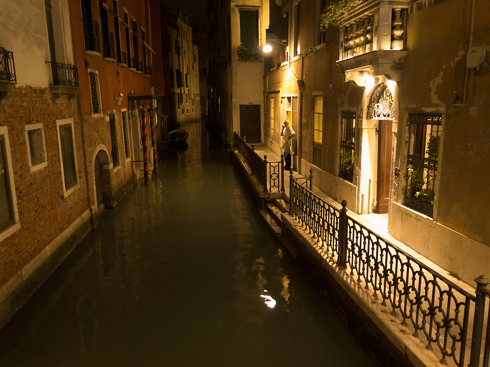 Chef taking a break and talking on a cell phone at night in a Venice canal