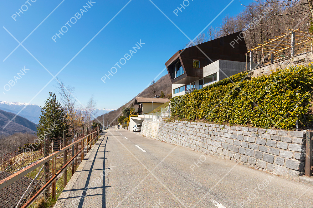Exterior modern isolated villa, surrounded by nature. Iron and concrete cladding. Front road deserted. Nobody inside