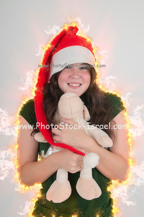Digitally enhanced image of a Young teen wearing Santa's helper hat and hugging a stuffed Teddy bear with Christmas atmosphere