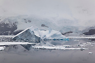 Ripple-free calmness allows great reflections of icebergs in the water along the coast of Peter 1 Øy, Phantom Coast, Bellingshausen Sea, West Antarctica
