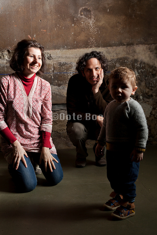 Portrait of happy mother and father with toddler in studio