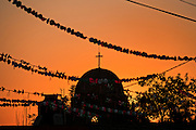 Sunset over a church at a village stop along the road during the annual Cabalgata de Cristo Rey pilgrimage January 4, 2017 in La Sauceda, Guanajuato, Mexico. Thousands of Mexican cowboys and horse take part in the three-day ride to the mountaintop shrine of Cristo Rey stopping along the way at shrines and churches.