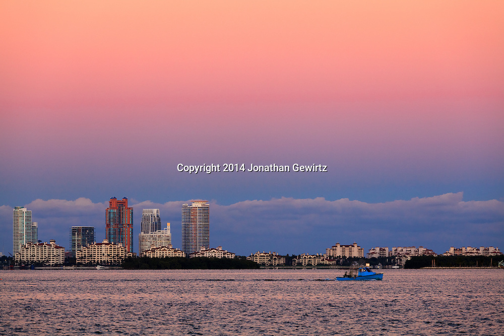 A fishing boat cruises through Biscayne Bay at sunset, past Fisher Island and South Beach condo buildings.<br /> WATERMARKS WILL NOT APPEAR ON PRINTS OR LICENSED IMAGES.