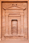 Modern inscriptions and graffiti on a carved facade in Petra, Jordan.