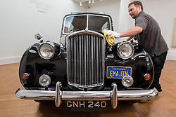 "© Licensed to London News Pictures. 12/08/2016. London, UK. A technician polishes the bonnet of John Lennon's iconic 1956 Austin Princess Limousine Hearse, immortalised in John Lennon and Yoko Ono's 1972 film ""Imagine"" (est. GBP 250,000) at the photocall for classic cars at Sotheby's, New Bond Street, ahead of their auction on 7 September in Battersea Park. Photo credit : Stephen Chung/LNP"