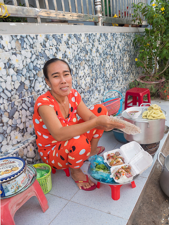 Asia, Vietnam, Mui Ne. Woman eating street food. Editorial Use Only.