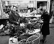 Moore Street traders prepare bunches of holly for Christmas, while under the table a boy sits beside nets of Brussels sprouts and Christmas hams hang in the butcher's shop window. Dublin<br /> 23/12/1975