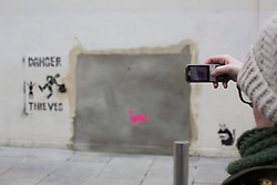 © licensed to London News Pictures. London, UK 22/02/2013. A woman taking picture of the graffitis thought to be Banksy's new work appears at the site of 'stolen' mural in Turnpike Lane, next to a Poundland branch. Photo credit: Tolga Akmen/LNP