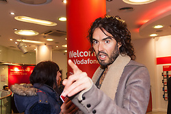 Oxford Street, London, December 5th 2014. Actor and Comdeian turned political activist Russel Brand visits several big brands'  stores including Boots, Apple and Vodafone in London accusing them of dodging tax whilst those most in need of benefits are facing cuts and increased hardship. A leaflet being distributed by him claims £14 billion is lost every year, through tax avoidance and loopholes exploited by big business. PICTURED: Russel Brand enters the Vodafone store in Oxford Street.