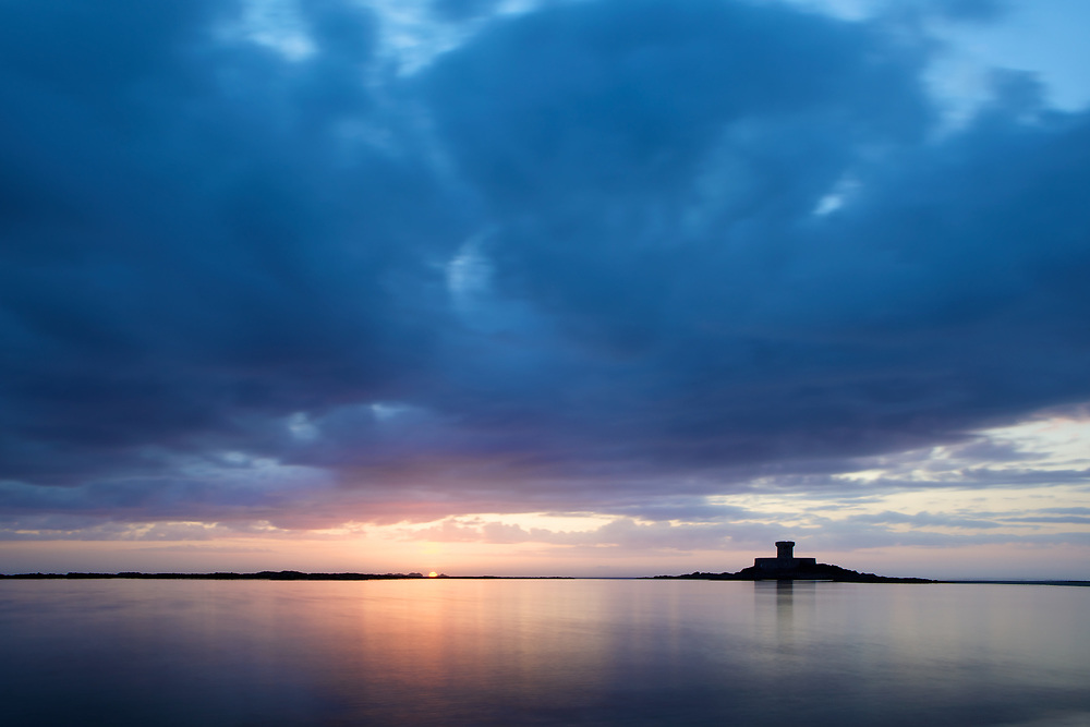 Glassy calm water at sunset at Le Rocco Tower, St ouen's Bay, Jersey, Channel Islands