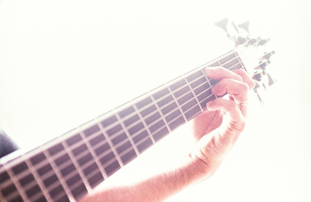 A closeup of a mans hands playing a bass guitar.