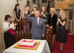 The Prince of Wales cuts into a cake after watching a performance by The Tootsie Rollers perform, as he hosts a reception to celebrate the 20th anniversary of the Walk the Walk charity at Clarence House, London.