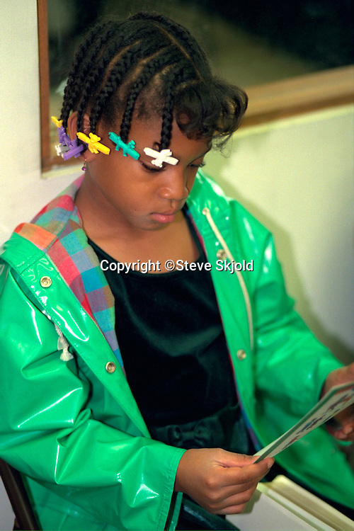 Sunday school student age 10  reading booklet during class.  St Paul Minnesota USA