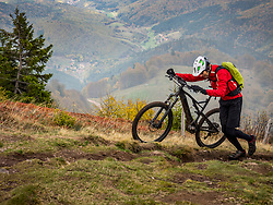 Man walking electric mountain bike on cycling tour, Vosges, France