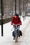 Een fietser rijdt op de Zijpendaalseweg in Arnhem door de sneeuw. Op de weg is niet gestrooid.<br /> <br /> A woman is cycling at the Zijpendaalseweg in Arnhem in the snow.