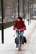 Een fietser rijdt op de Zijpendaalseweg in Arnhem door de sneeuw. Op de weg is niet gestrooid.<br /> <br /> A woman is cycling at the Zijpendaalseweg in Arnhem in the snow.