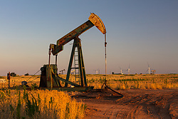 Pump jack in a rural Texas field with wind turbines on the horizon at dusk.
