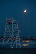 USA, Newport, RI - Full moon rises over life guard chair five at first (Easton's) beach