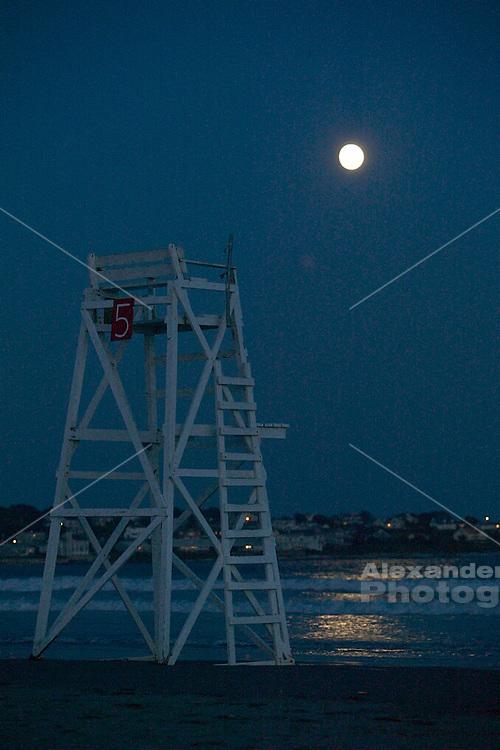USA, Newport, RI - Full moon rises over life guard chair five at first (Easton's) beach