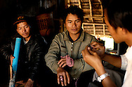Burma/Myanmar, nearby Kentung.  Akha men waiting for an advice on the wounded hand problem.