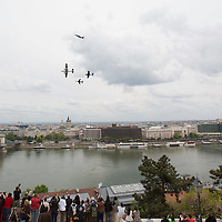 People photograph an old-timer plane formation during an air show above river Danube crossing central Budapest, Hungary on May 01, 2016. ATTILA VOLGYI