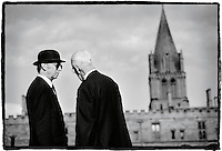 Black and white photo of two men talking outside of Christ Church in Oxford, England.