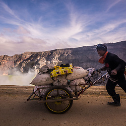 A miner with a full load of sulfur starts rolling down his trolley to the checkpoint - which is 3km downhill. It will take him about an hour. He still had to carry up the load to the rim, roughly 175 vertically up. Trolleys cost about 2 million Rupiah (150 USD). Not all of the miners can afford one. Most of the trolleys are coming from donations.