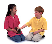 Young Boy and Girl, aged 8 years old, holding and stroking guinea pig, studio, white background, cut out, pet