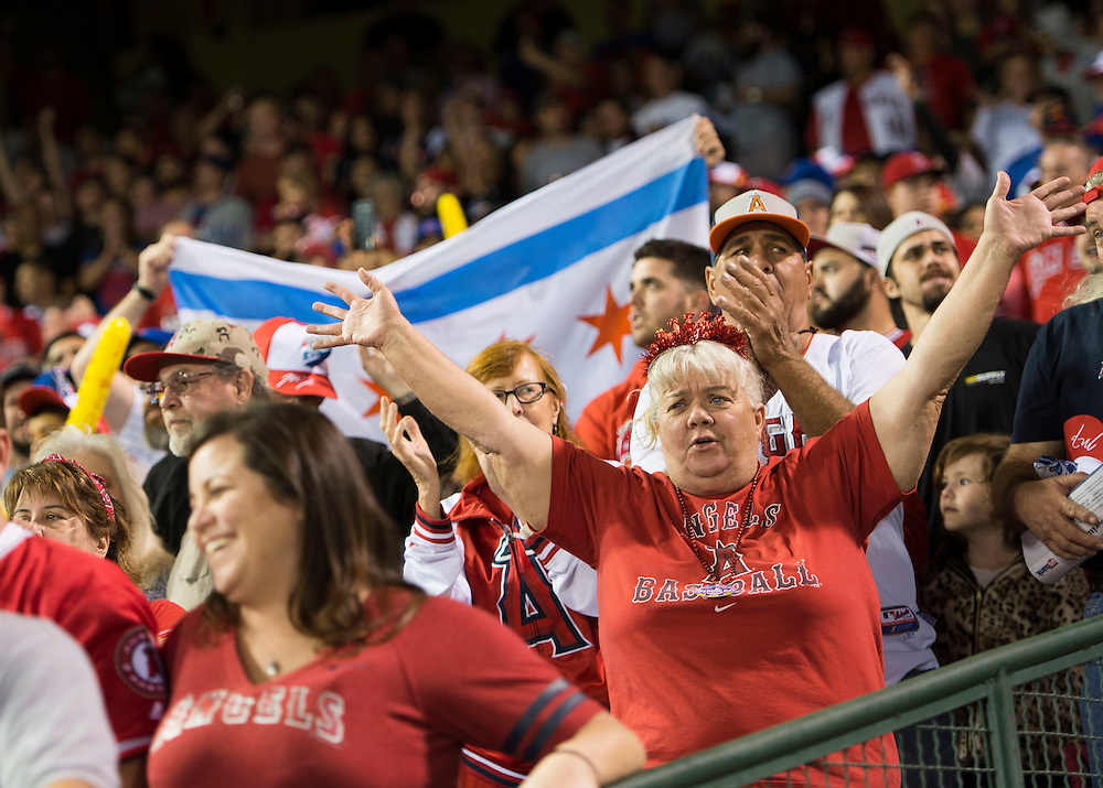 Angel fans cheer during the seventh inning stretch during the Angels' home opener Monday at Angel Stadium.<br /> <br /> ///ADDITIONAL INFO:   <br /> <br /> angels.0405.kjs  ---  Photo by KEVIN SULLIVAN / Orange County Register  --  4/4/16<br /> <br /> The Los Angeles Angels take on the Chicago Cubs during their 2016 home opener Monday at Angel Stadium.<br /> <br /> <br />  4/4/16