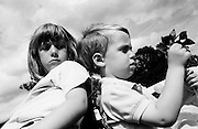 """Seen from a low angle, we see a big sister turning around to see what her younger brother is up to as they sit back-to-back in a park in London, England. The boy is actually playing with the girl's toy windmill, turning its sails proving a fun way of passing part of a summer's afternoon in this inner-city park. His sister is unimpressed however and she is about to snatch her own property back - not because she needs it, but simply because it is hers. These siblings are having to learn sharing each other's things and as a five and three year-old are finding out, it's a hard lesson. From a personal documentary project entitled """"Next of Kin"""" about the photographer's two children's early years spent in parallel universes. Model released."""