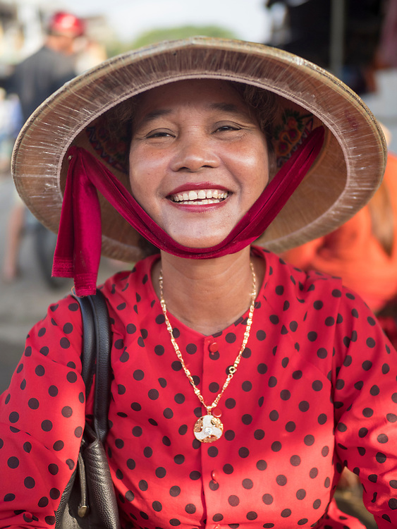 Asia, Vietnam, Hoi An, old town historic district.  UNESCO World Heritage Site. Woman in traditional Non La conical hat and red and black spotted blouse. Editorial Use Only.