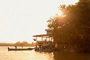 View of the exterior of Hotel Sabalos on the bank of San Juan River and boats under the shining sun at sunset, El Castillo, Rio San Juan Department, Nicaragua