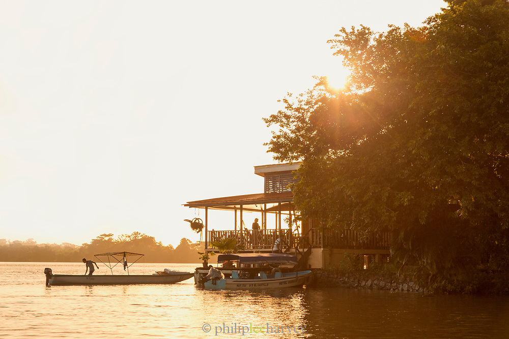 View of the exterior of Hotel Sabalos on the bank of San Juan River and boats under the shining sun at sunset, El Castillo, Rio San Juan Department, Nicaragua
