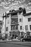 A black and white view of Le Brasserie Saint-Maurice a restaurant specializing in business lunches and seminars, and their gorgeous Neo-Classic French building, Old Annecy, France.