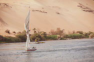 A group of tourists sail in a felucca on the Nile River past the picturesque sand dunes in Aswan, Egypt.