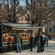 Food stall in Paris park selling coffee and pastries to passers by.