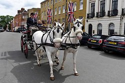 © Licensed to London News Pictures. 11/05/2018. WINDSOR, UK.  Tourists in a horsedrawn carriage pass by on a decorated Park Street in Windsor ahead of the upcoming wedding between Prince Harry and Meghan Markle on 19 May.  The newly married couple will ride their own horsedrawn carriage through the town as thousands of people are expected to visit the town for what has been billed as the wedding of the year.  Photo credit: Stephen Chung/LNP