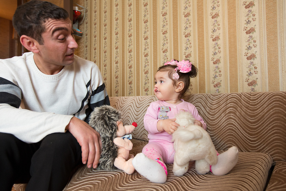 CAPTION: Stella's father Arman plays with her and her soft toys. When he took Stella to the polyclinic for her pre-surgery tests two months ago, it was found that her blood haemoglobin level was too low. Dr Fomenko therefore prescribed her medicine and instructed them to put her on a special diet. As they followed this well, all the signs show that she's now ready for surgery. LOCATION: Volgograd, Russia. INDIVIDUAL(S) PHOTOGRAPHED: Arman Aharonyan (left) and Stella Aharonyan (right).