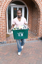 Man carrying curb side recycling collection box out of house onto pavement for collection,