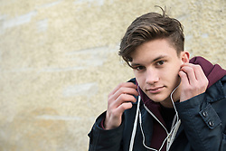 Portrait of a young man listening to music with earbud, Munich, Bavaria, Germany