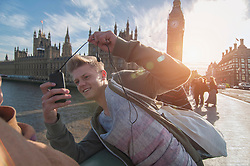 Boy takes pictures of his friend on bridge using mobile camera, Bavaria, Germany