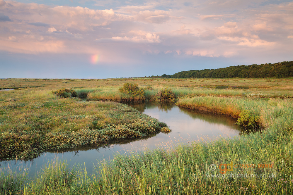 Stormy skies and a final remnant of a rainbow above Stiffkey's stunning salt marshes. North Norfolk coast, East Anglia, England, UK.