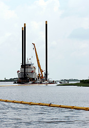 26 May 2010. Barataria Bay, Louisiana. <br /> A jack up rig is used as a command and control center for boom laying operations. The environmental and economic impact is devastating with many shrimp boats tied up, vacation rentals and charter boat fishing trips cancelled the only business for shrimpers is loading and laying boom and working for big oil. Oil from the Deepwater Horizon catastrophe is evading booms laid out to stop it thanks in part to the dispersants which means the oil travels at every depth of the Gulf and washes ashore wherever the current carries it. <br /> Photo credit; Charlie Varley<br /> www.varleypix.com