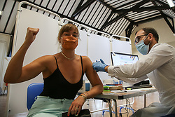 © Licensed to London News Pictures. 20/07/2021. London. Australian, Maxine Thompson gestures as vaccinator Moneer Said administers the second dose of Pfizer Covid-19 at a vaccination centre in Tottenham, north London, the day after Freedom Day. Maxine will now be able to travel to Australia to visit her parents after 2 years. In the press conference yesterday, Prime Minister Boris Johnson said that people will need to be double-jabbed before being allowed to enter nightclubs and other crowded venues. Photo credit: Dinendra Haria/LNP
