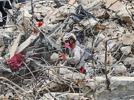 A search and rescue team member moves through the debris field of the 12-story oceanfront condo, Champlain Towers South, in Surfside on Friday, July 09, 2021.