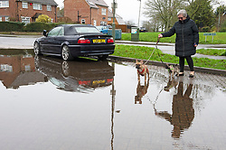 ©Licensed to London News Pictures 15/01/2020<br /> Orpington, UK. A lady walks her dogs along a flooded car park in Orpington, Kent after Storm Brendan hit the UK last night with heavy winds and rain. Photo credit: Grant Falvey/LNP