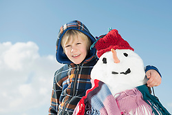 Portrait of boy standing with snowman, smiling, Bavaria, Germany