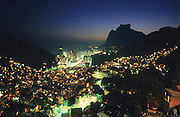 FAVELA SLUM NIEGHBOURHOOD, Rio de Janeiro, Brazil, South America. View across Rocinha Favela showing the slum and Rio at night. Although Rocinha is technically classified as a neighborhood, many still refer to it as a favela. It developed from a shanty town into an urbanized slum. Today, almost all the houses in Rocinha are made from concrete and brick. Some buildings are three and four stories tall and almost all houses have basic sanitation, plumbing, and electricity. Compared to simple shanty towns or slums, Rocinha has a better developed infrastructure and hundreds of businesses. There is also lots of deliquency, crime and drugs in the favelas.